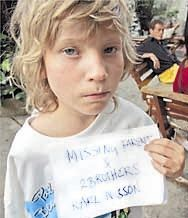 "A young swedish boy holds a sign that says ""Missing Parents and 2 Brothers"""